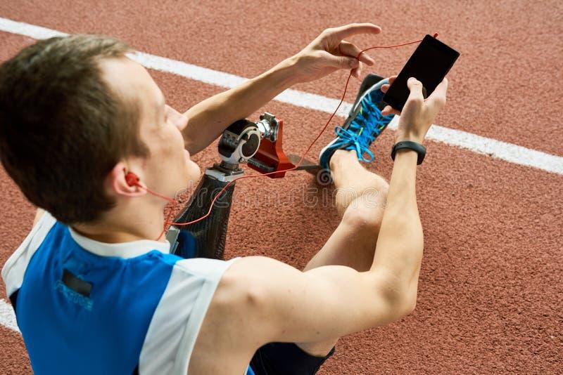 Ανάπηρος αθλητικός τύπος που ακούει τη μουσική στοκ εικόνες