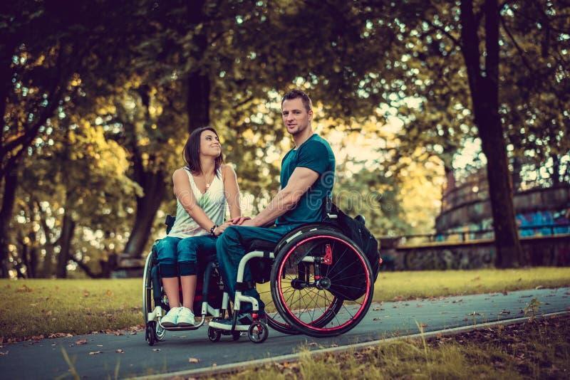Ανάπηρο νέο ζεύγος σε δύο αναπηρικές καρέκλες στοκ φωτογραφία