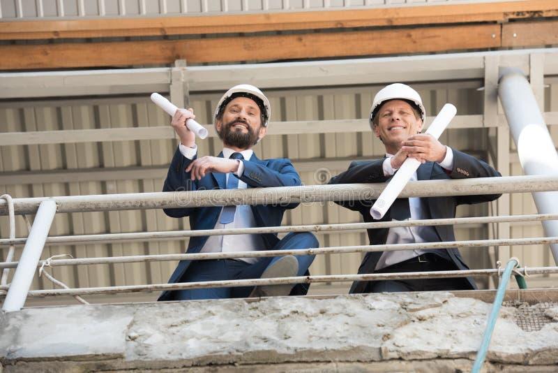 Ανάδοχοι στα κοστούμια που εξετάζουν τη κάμερα στο εργοτάξιο οικοδομής στοκ εικόνα