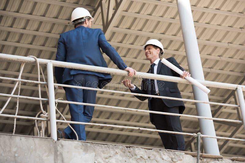 Ανάδοχοι στην επίσημη ένδυση που μιλούν στο εργοτάξιο οικοδομής στοκ εικόνες