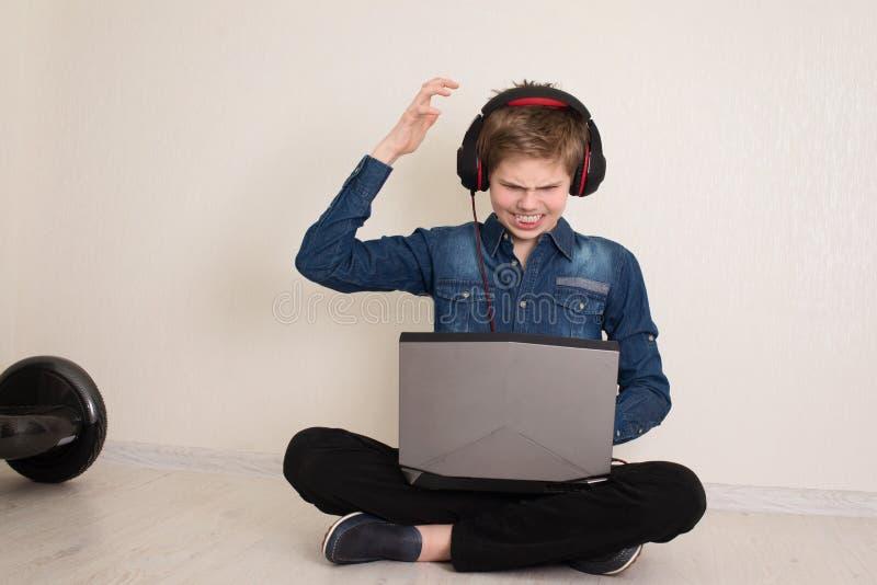 Ανήσυχος και λυπημένος έφηβος μαθητής με χέρια στο κεφάλι, αφότου διάβασε άσχημα νέα στην γραμμή, με φορητό υπολογιστή στα γόνατα στοκ εικόνες