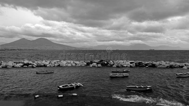 Ανήσυχος κόλπος της Νάπολης που αγνοεί το Βεζούβιο και τις όμορφες βάρκες στο πρώτο πλάνο μαύρο λευκό στοκ εικόνες