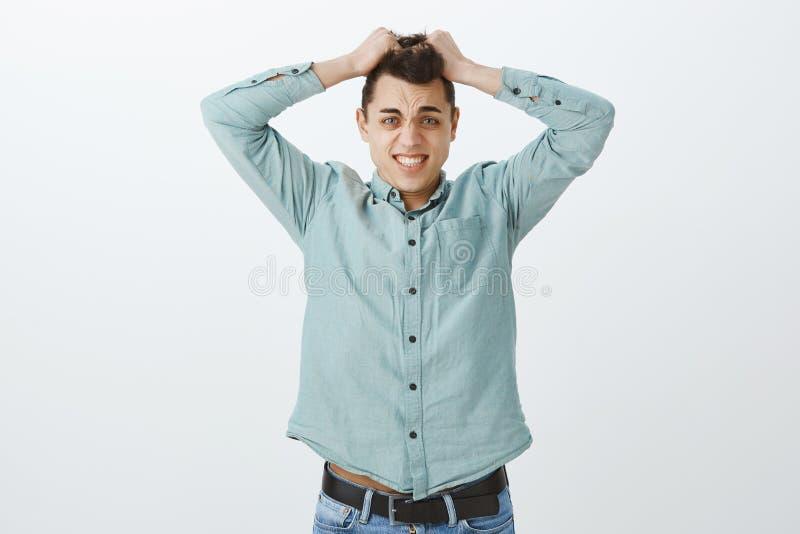 Ανήσυχος συντριμμένος ενήλικος συνάδελφος στο περιστασιακό πουκάμισο, που βγάζει την τρίχα και που μορφάζει από τη νευρικότητα κα στοκ φωτογραφία