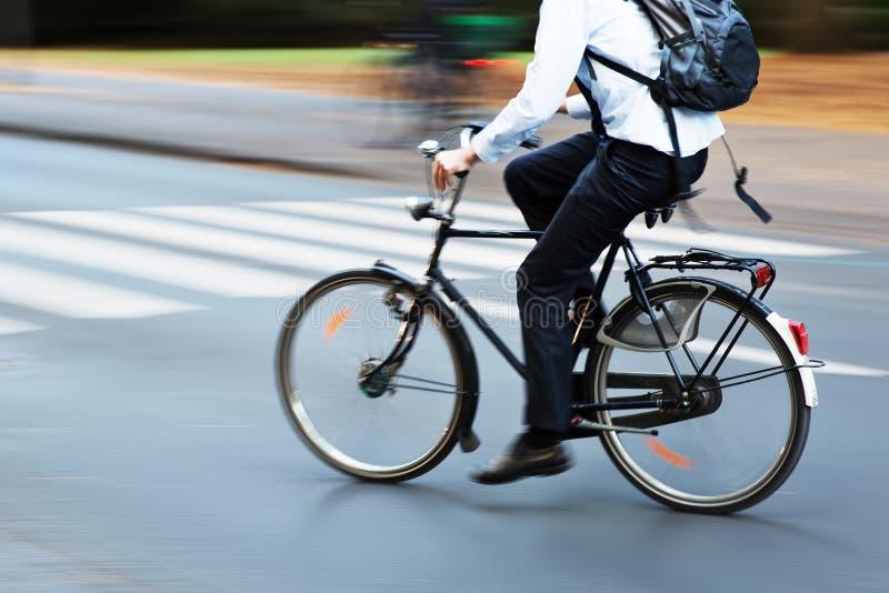 Αναβάτης ποδηλάτων στην κυκλοφορία πόλεων στη θαμπάδα κινήσεων στοκ φωτογραφία