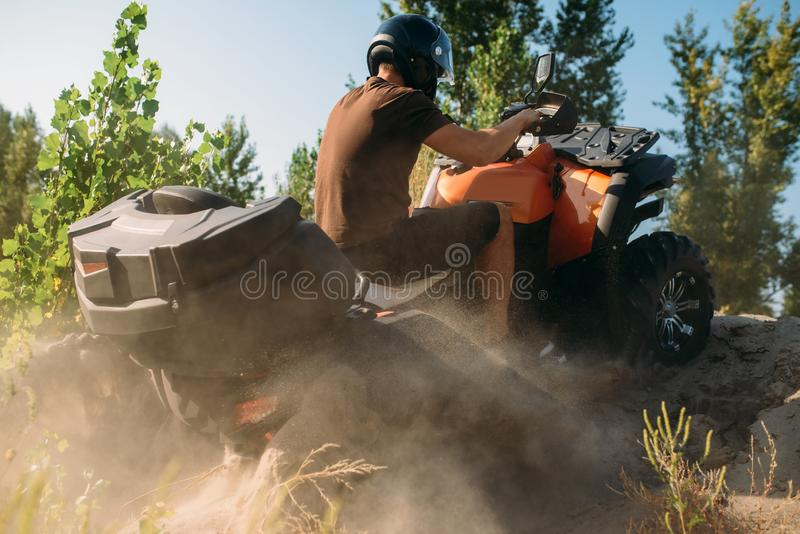 Αναβάτης Atv που αναρριχείται στο βουνό άμμου, πίσω άποψη στοκ εικόνα με δικαίωμα ελεύθερης χρήσης
