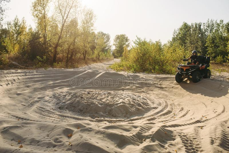 Αναβάτης Atv στο κράνος που αναρριχείται στον αμμώδη δρόμο στο δάσος στοκ εικόνες με δικαίωμα ελεύθερης χρήσης