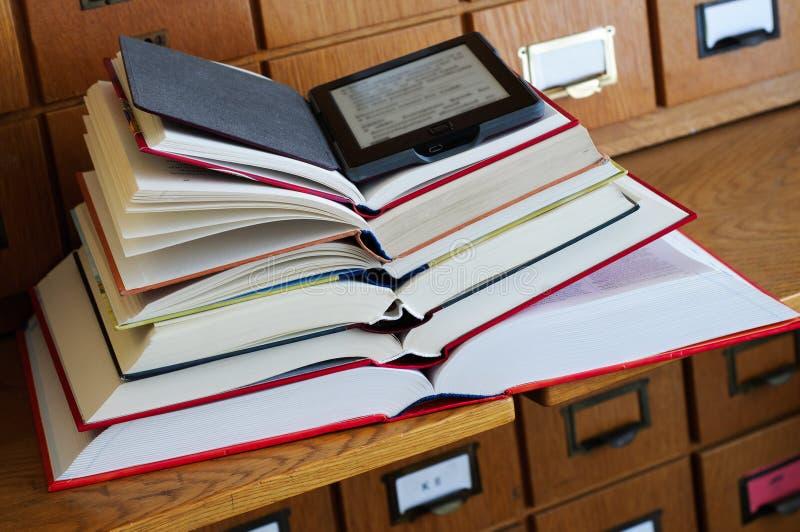 Αναγνώστης EBook πάνω από το σωρό των βιβλίων σε μια βιβλιοθήκη στοκ εικόνες με δικαίωμα ελεύθερης χρήσης