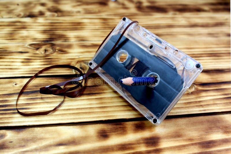 Αναδρομικά ακουστικά κασέτα και μολύβι σε έναν ξύλινο πίνακα Παλαιό μαγνητικό μέσο απομνημόνευσης στοκ φωτογραφία