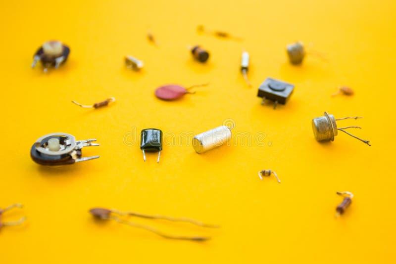 Αναδρομικά ηλεκτρονικά συστατικά που απομονώνονται στο κίτρινο υπόβαθρο, έννοια απεικόνιση αποθεμάτων