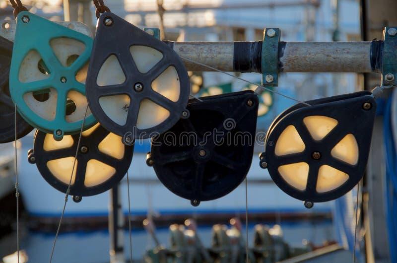 Αναδρομικά φωτισμένες τροχαλίες σε μια εμπορική πυράκτωση αλιευτικών σκαφών λαμβάνοντας υπόψη τον ήλιο ρύθμισης στοκ φωτογραφίες με δικαίωμα ελεύθερης χρήσης