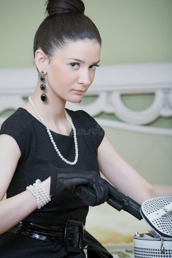 Αναδρομική γυναίκα με ένα πυροβόλο όπλο σε μια γυναίκα ξενοδοχείων στοκ φωτογραφία με δικαίωμα ελεύθερης χρήσης