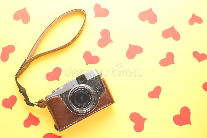 Αναδρομική κάμερα φωτογραφιών ύφους και κόκκινες καρδιές εγγράφου στο κίτρινο υπόβαθρο στοκ εικόνες με δικαίωμα ελεύθερης χρήσης