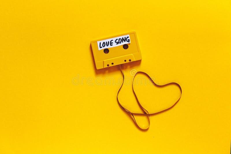 Αναδρομική κασέτα ήχου με το ερωτικό τραγούδι επιγραφής σε ένα κίτρινο υπόβαθρο, τοπ άποψη Ρωμανική έννοια στοκ εικόνα με δικαίωμα ελεύθερης χρήσης