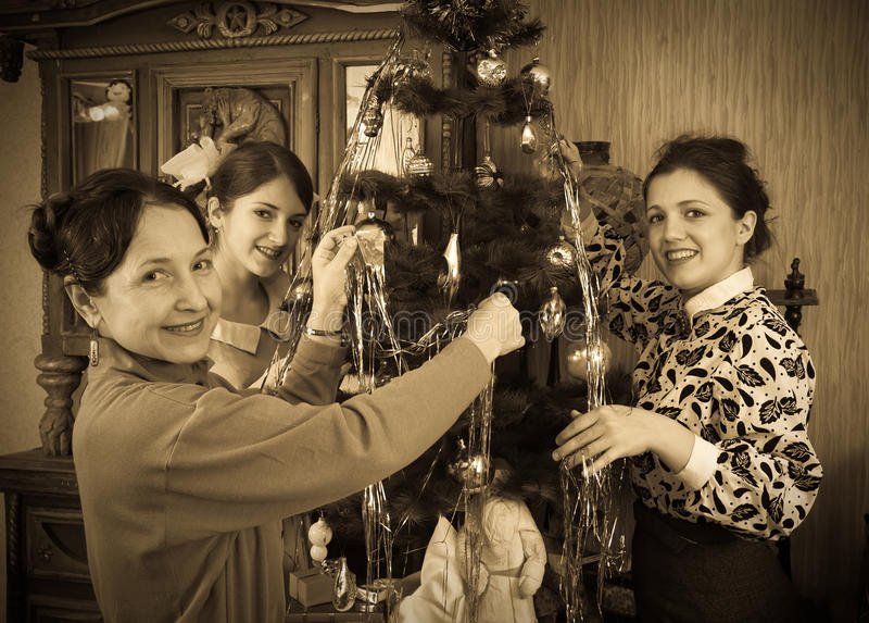 Αναδρομική φωτογραφία των κοριτσιών με τη μητέρα στο χριστουγεννιάτικο δέντρο στοκ εικόνες