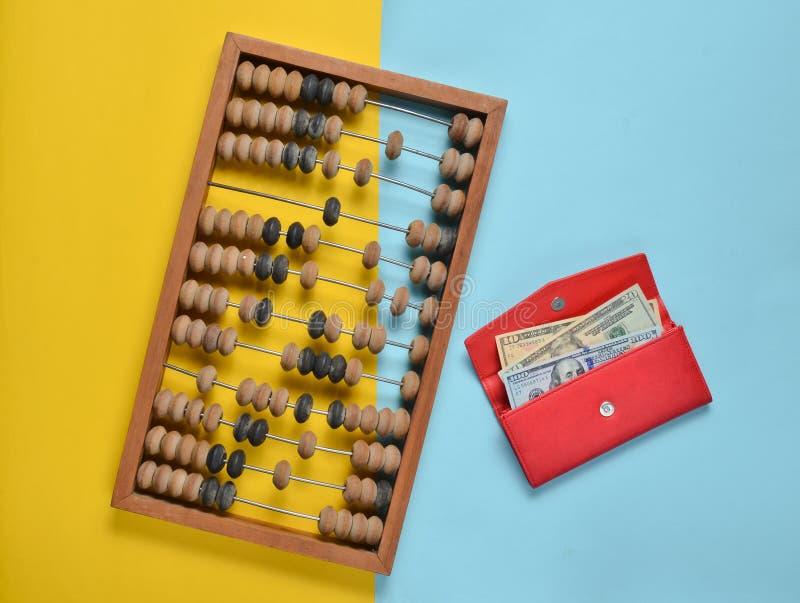Αναδρομικός ξύλινος άβακας, κόκκινο πορτοφόλι δέρματος με τους λογαριασμούς δολαρίων σε ένα χρωματισμένο υπόβαθρο εγγράφου Τοπ όψ στοκ εικόνα με δικαίωμα ελεύθερης χρήσης