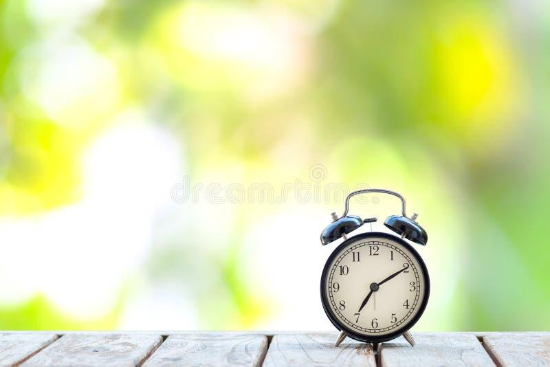 Αναδρομικό μαύρο ξυπνητήρι στον ξύλινο πίνακα στοκ φωτογραφία με δικαίωμα ελεύθερης χρήσης