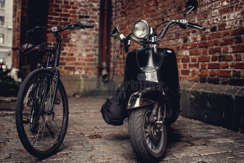 Αναδρομικό μηχανικό δίκυκλο moto και μαύρο ποδήλατο στοκ φωτογραφίες με δικαίωμα ελεύθερης χρήσης