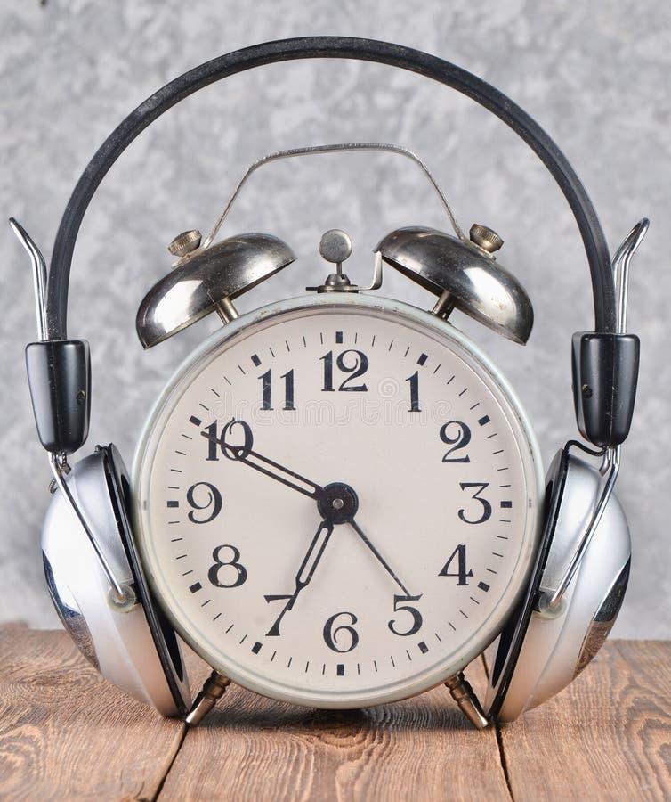 Αναδρομικό ξυπνητήρι με τα ακουστικά στον ξύλινο πίνακα στο γκρίζο υπόβαθρο συμπαγών τοίχων στοκ εικόνα