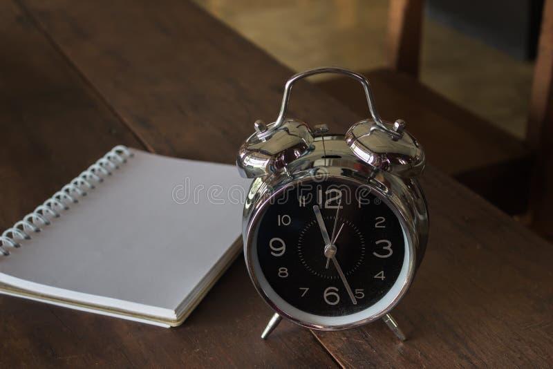 Αναδρομικό ξυπνητήρι με το κενό ρεαλιστικό σπειροειδές σημειωματάριο ο σημειωματάριων στοκ εικόνες με δικαίωμα ελεύθερης χρήσης