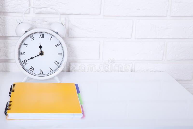 Αναδρομικό ξυπνητήρι με το σημειωματάριο κοντά στο τουβλότοιχο στον άσπρο εργασιακό χώρο Εκλεκτική εστίαση χρυσή ιδιοκτησία βασικ στοκ εικόνα με δικαίωμα ελεύθερης χρήσης