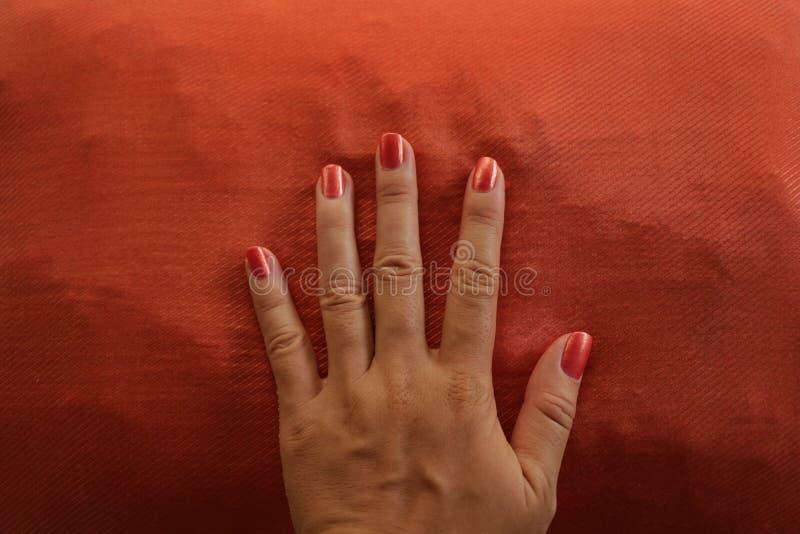 Αναδρομικό χρωματισμένο χέρι πορτοκάλι Manicured στο ταίριασμα του υποβάθρου στοκ φωτογραφία
