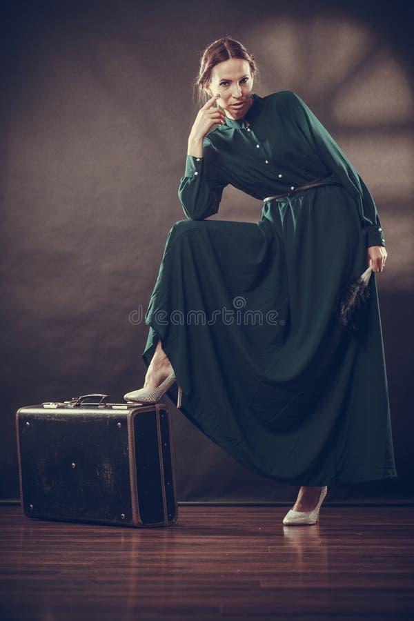 Αναδρομικό ύφος γυναικών με την παλαιούς βαλίτσα και τον ανεμιστήρα στοκ εικόνες