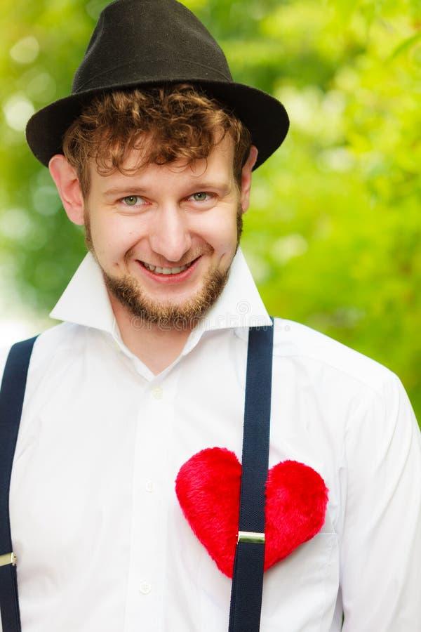 Αναδρομικό ύφος νεαρών άνδρων με την κόκκινη καρδιά στο στήθος στοκ φωτογραφία