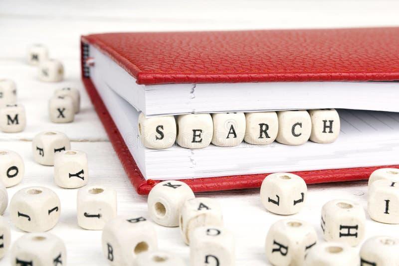 Αναζήτηση λέξης που γράφεται στους ξύλινους φραγμούς στο σημειωματάριο άσπρο σε ξύλινο στοκ εικόνα με δικαίωμα ελεύθερης χρήσης