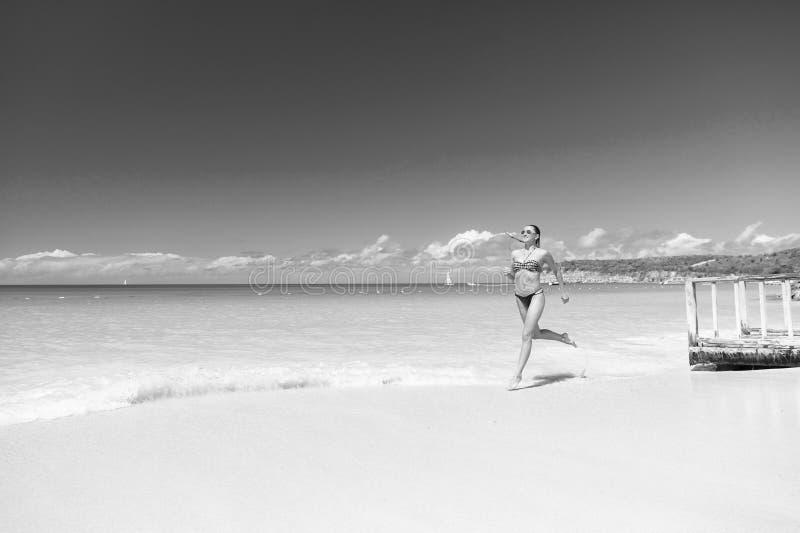 Αναζωογονημένος και χαρούμενος Το μπικίνι κοριτσιών τρέχει την κυανή ωκεάνια παραλία κυμάτων Τροπικό ωκεάνιο παραθαλάσσιο θέρετρο στοκ εικόνες