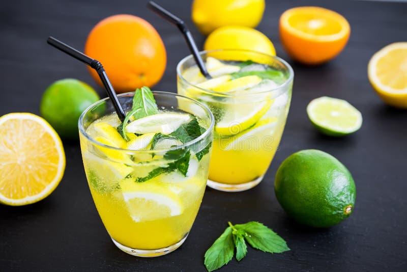 Αναζωογονώντας λεμονάδα στο γυαλί με τους ασβέστες, τα λεμόνια και το πορτοκάλι στοκ εικόνα με δικαίωμα ελεύθερης χρήσης