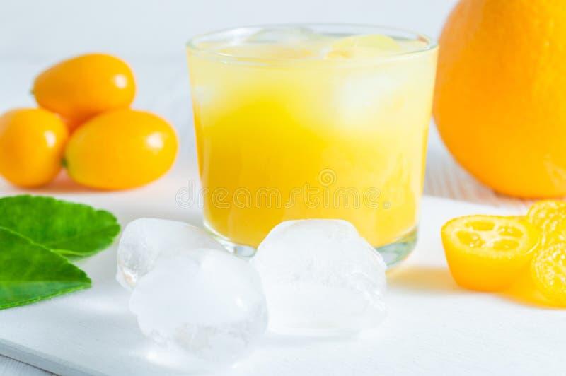 Αναζωογονώντας ποτό θερινών εσπεριδοειδών με τους κύβους πορτοκαλιών, κουμκουάτ και πάγου στον άσπρο ξύλινο πίνακα στοκ εικόνες