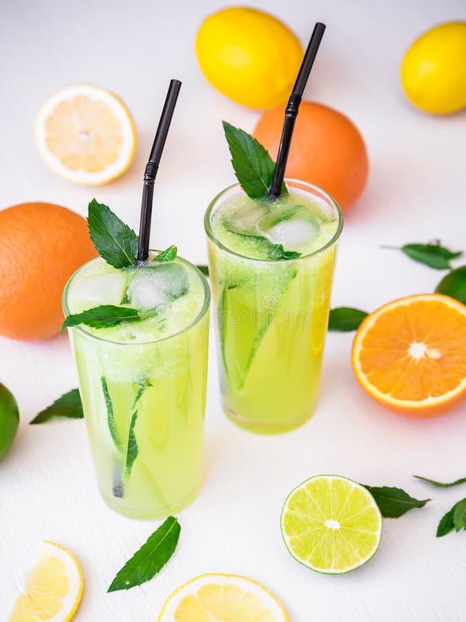 Αναζωογονώντας ποτό με το αγγούρι, τους ασβέστες και το πορτοκάλι απομονωμένο κοκτέιλ θερινό τονωτικό λευκό στοκ φωτογραφία
