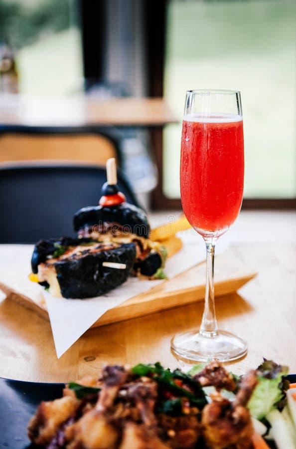 Αναζωογόνηση της κόκκινης διάτρησης κοκτέιλ με στο γυαλί λαμπιρίζοντας κρασιού στο Di στοκ φωτογραφίες