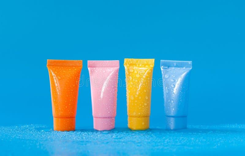 Αναζωογόνηση των καλλυντικών προϊόντων υγιεινής προσοχής σωμάτων στους χρωματισμένους σωλήνες Αφηρημένο μπλε κίτρινο ρόδινο πορτο στοκ εικόνες