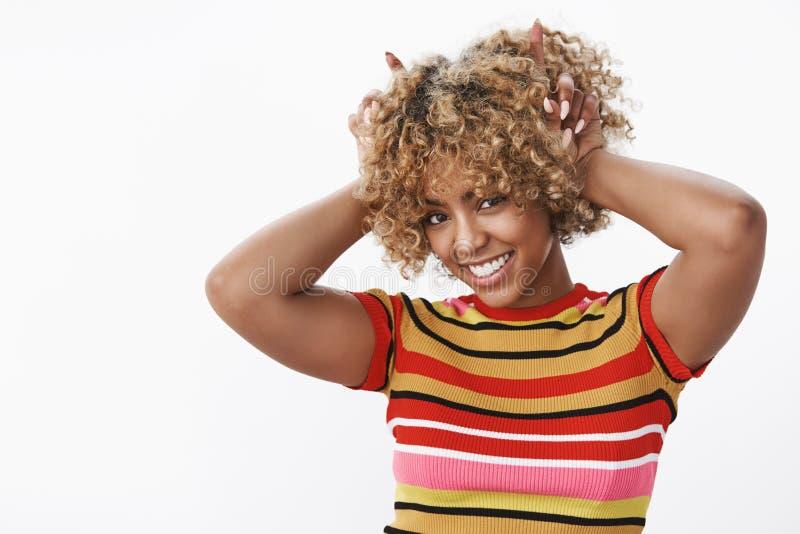 Αναιδές και αστείο flirty κορίτσι αφροαμερικάνων που παρουσιάζει κέρατα, εκφράζοντας τη διαβολική και ξένοιαστη φύση, που χαμογελ στοκ εικόνα