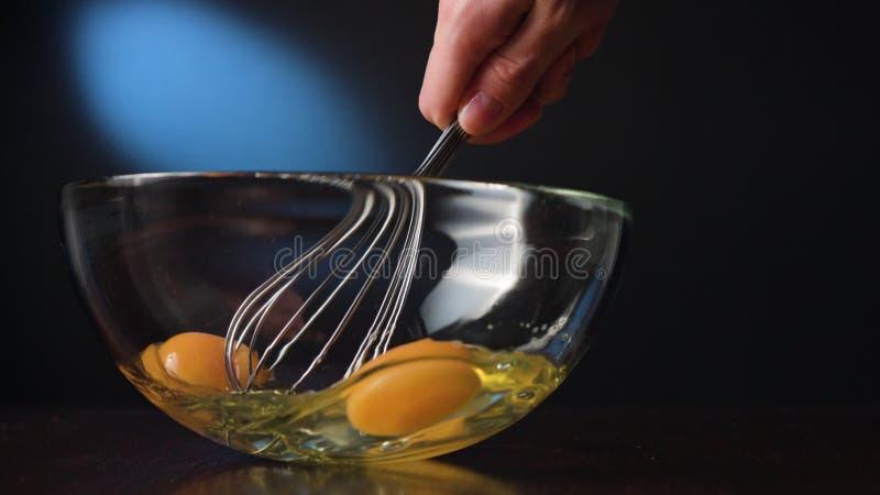 Ανακάτωμα των αυγών σε ένα κύπελλο γυαλιού με ένα μουστάκι στοκ εικόνες