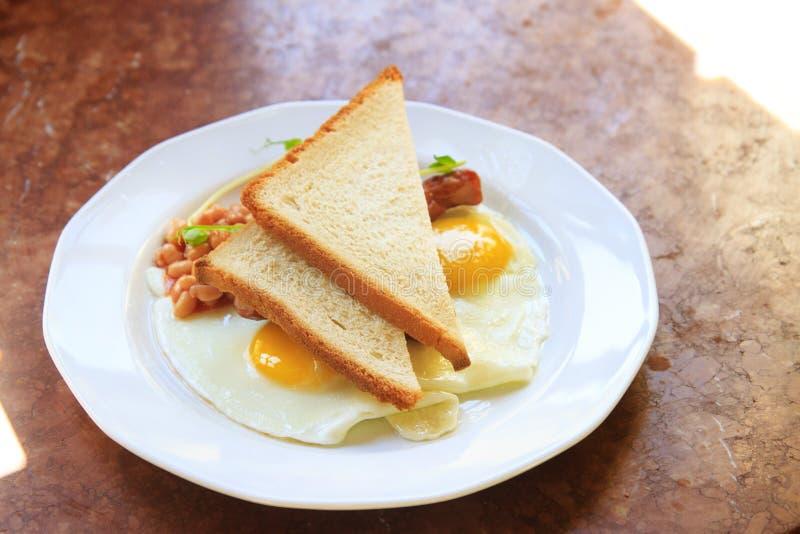 Ανακατωμένα αυγά με τα φασόλια και φρυγανιά σε ένα άσπρο πιάτο στοκ φωτογραφία με δικαίωμα ελεύθερης χρήσης