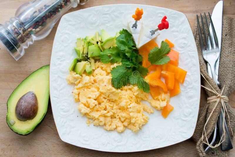 Ανακατωμένα αυγά με την πράσινα και πορτοκαλιά πάπρικα και το αβοκάντο στοκ εικόνα με δικαίωμα ελεύθερης χρήσης