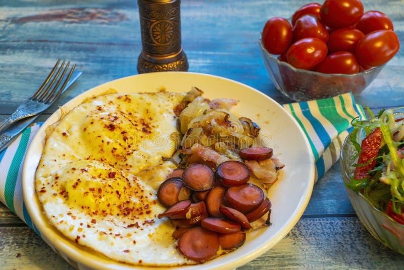 Ανακατωμένα αυγά με το μπέϊκον, το κρεμμύδι και το λουκάνικο στοκ εικόνες