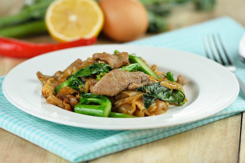 Ανακατώνω-τηγανισμένα νουντλς με το χοιρινό κρέας και το κινεζικό μπρόκολο στοκ εικόνες
