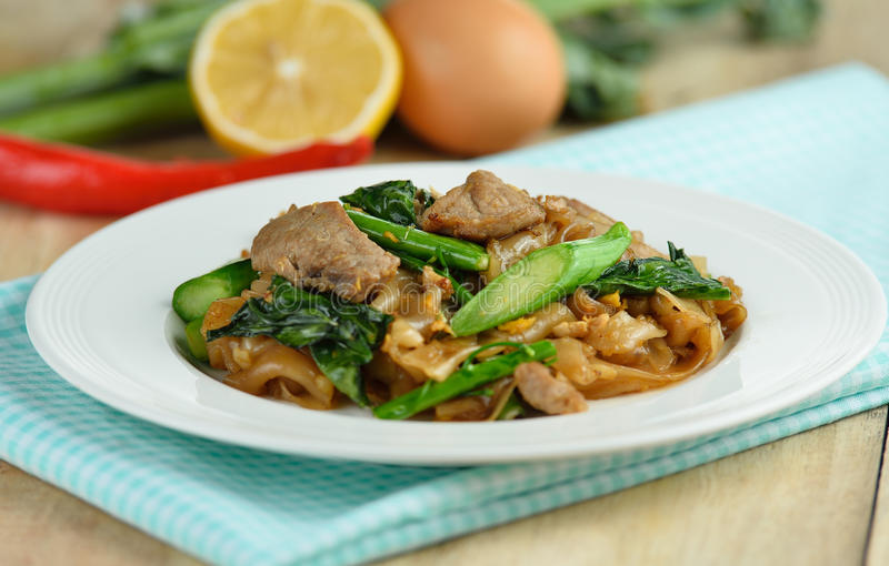Ανακατώνω-τηγανισμένα νουντλς με το χοιρινό κρέας και το κινεζικό μπρόκολο στη γλυκιά σόγια στοκ εικόνα με δικαίωμα ελεύθερης χρήσης