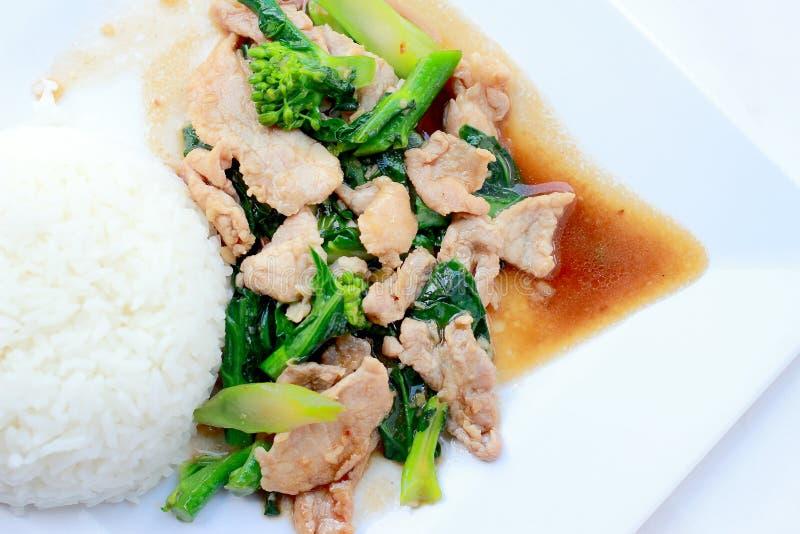 Ανακατώνω-τηγανισμένο μπρόκολο με το χοιρινό κρέας με το ρύζι στο άσπρο πιάτο στο άσπρο υπόβαθρο, ταϊλανδικά τρόφιμα στοκ φωτογραφίες