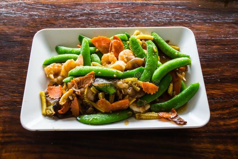 Ανακατώστε τα βαλμένα φωτιά τοπικά λαχανικά με τις γαρίδες στο πιάτο στοκ φωτογραφίες
