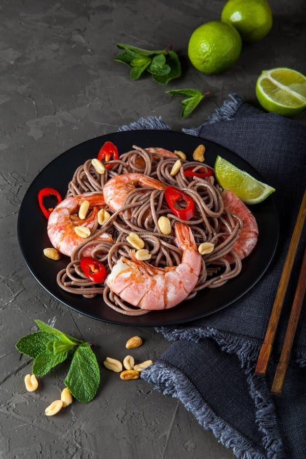 Ανακατώστε τα νουντλς τηγανητών με τα λαχανικά και τις γαρίδες στο μαύρο κύπελλο στοκ φωτογραφία με δικαίωμα ελεύθερης χρήσης