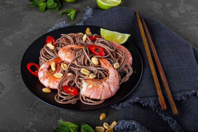 Ανακατώστε τα νουντλς τηγανητών με τα λαχανικά και τις γαρίδες στο μαύρο κύπελλο στοκ εικόνα