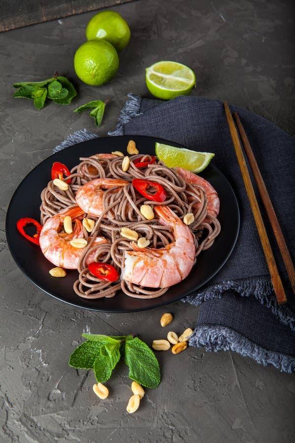 Ανακατώστε τα νουντλς τηγανητών με τα λαχανικά και τις γαρίδες στο μαύρο κύπελλο στοκ εικόνα με δικαίωμα ελεύθερης χρήσης
