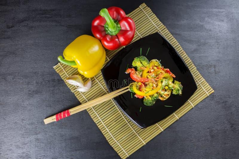 Ανακατώστε τα νουντλς τηγανητών με τα λαχανικά σε ένα μαύρο πιάτο με τα συστατικά σε ένα χαλί μπαμπού, μαύρο υπόβαθρο, τοπ άποψη στοκ εικόνα