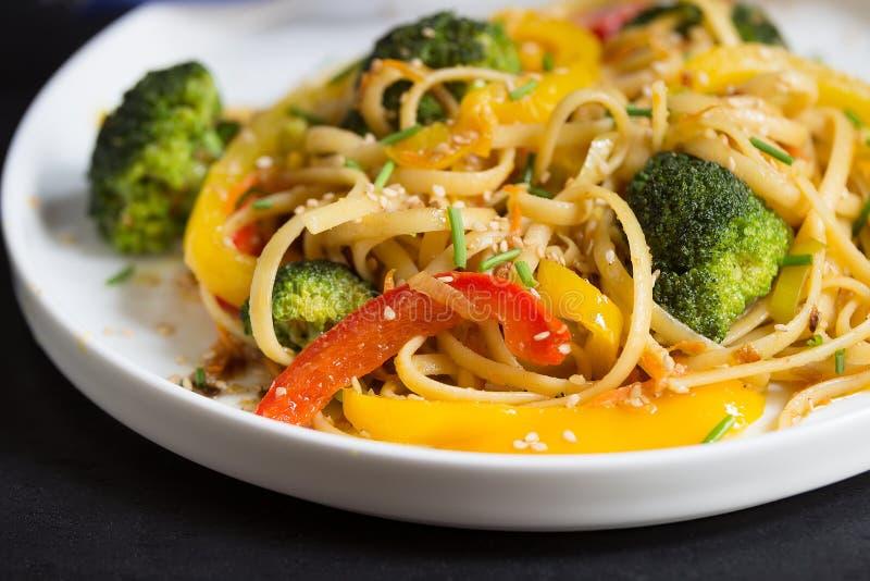 Ανακατώστε τα νουντλς τηγανητών udon με τα λαχανικά στο μαύρο υπόβαθρο, που μαγειρεύεται στο wok, κλείστε επάνω στοκ φωτογραφίες με δικαίωμα ελεύθερης χρήσης