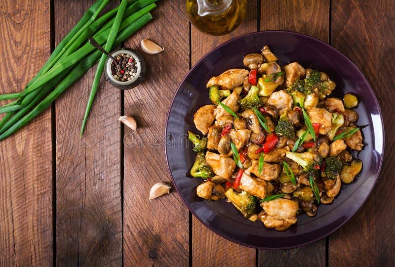 Ανακατώστε τα τηγανητά με το κοτόπουλο, τα μανιτάρια, το μπρόκολο και τα πιπέρια στοκ εικόνες