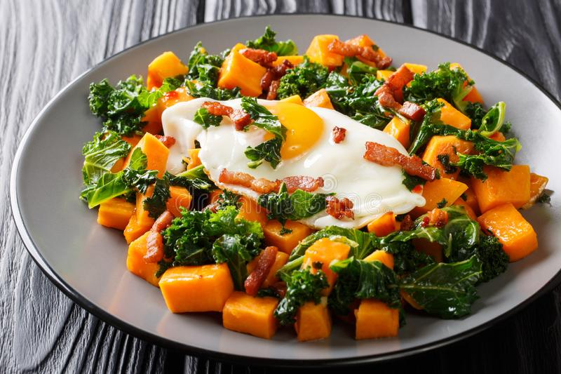 Ανακατώστε τα τηγανητά των γλυκών πατατών με το κατσαρό λάχανο που εξυπηρετείται με το μπέϊκον και την τηγανισμένη κινηματογράφησ στοκ φωτογραφίες με δικαίωμα ελεύθερης χρήσης